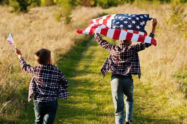 Deux frères courant avec le drapeau des etats-unis. fête de l'amérique. fiers d'être des enfants du pays.