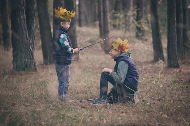 Deux frères courir dans une forêt le jour de l'automne.