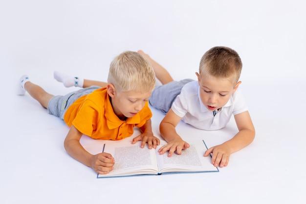 Deux frères garçons d'âge préscolaire mentent et lisent un livre