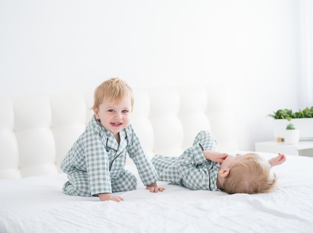 Deux frères garçons heureux sur lit blanc en pyjama s'amusant ensemble