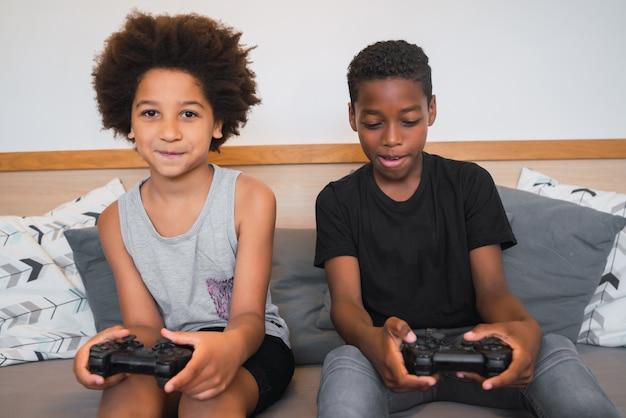 Deux frères jouant à des jeux vidéo à la maison.