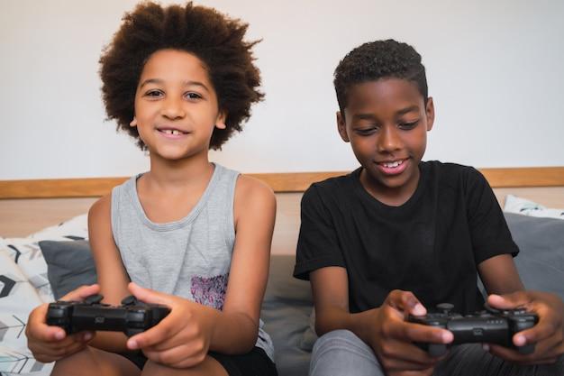 Deux frères jouent à des jeux vidéo à la maison.