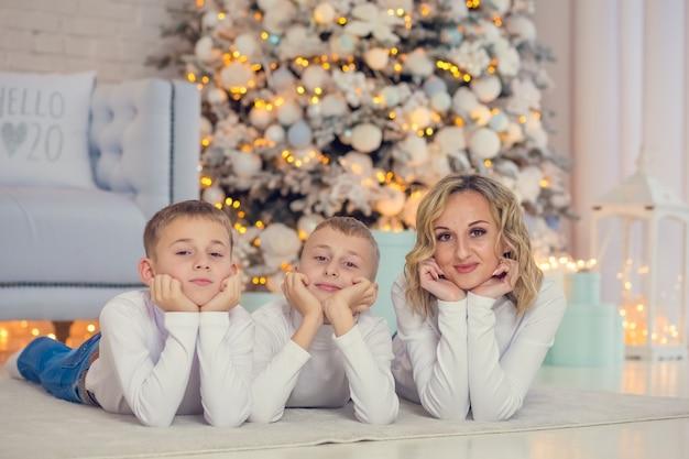 Deux frères et leur maman se trouvent près de l'arbre de noël à noël