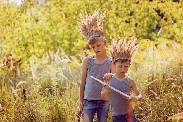 Deux frères ont une couronne d'herbe sèche sur la tête et des épées dans les mains. concept de joie et de jeu.