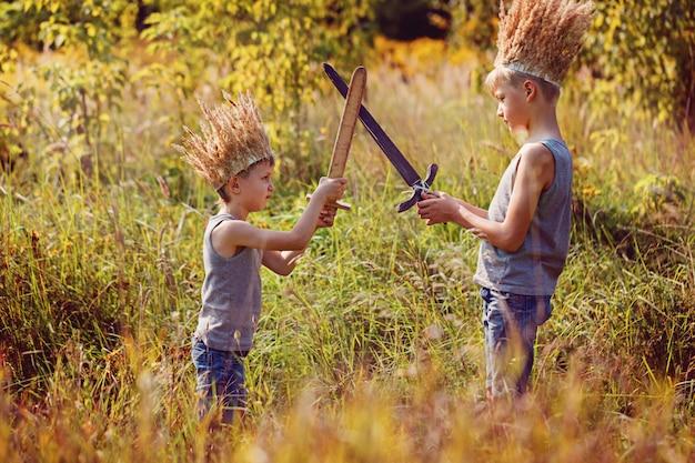 Deux frères ont une couronne d'herbe sèche sur la tête et des épées dans les mains.