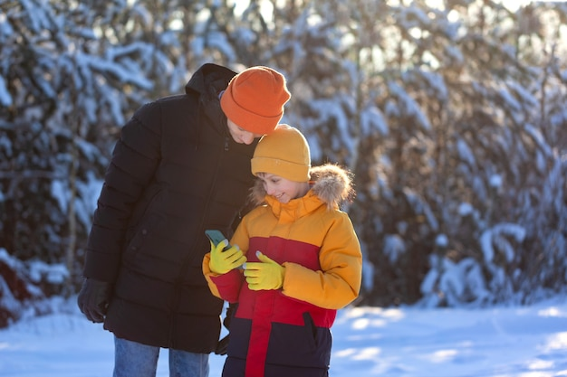 Deux frères portent un chapeau et un manteau en hiver à la recherche d'un téléphone portable et souriant sur le fond de la forêt d'hiver enneigée.