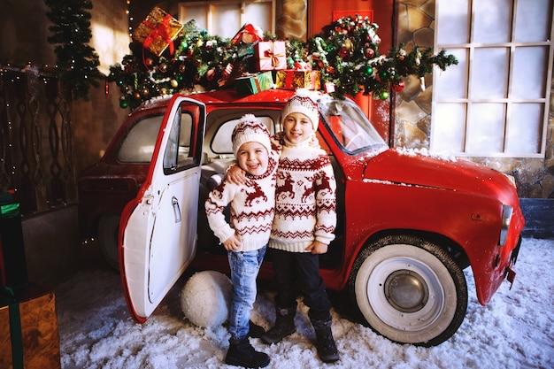 Deux frères en pulls tricotés avec des cerfs se tiennent près de la voiture rouge du nouvel an et se réjouissent de l'avènement de noël. enfant s'amusant à l'heure de la nativité. concept de vacances de noël.