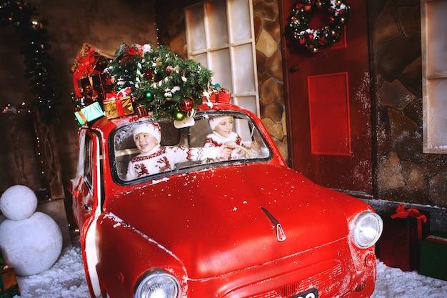 Deux frères en pulls tricotés avec des cerfs sont assis dans une voiture rouge du nouvel an et se réjouissent de l'avènement de noël. enfant s'amusant à l'heure de la nativité. concept de vacances de noël.