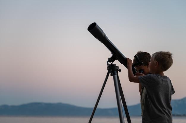 Deux frères regardant les étoiles à l'aide d'un télescope au bord de la mer