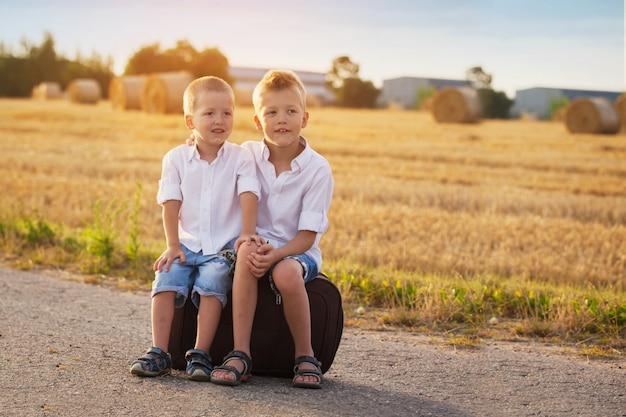 Deux frères s'asseoir sur une valise sur la route en été au coucher du soleil