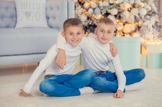 Deux frères s'embrassent, s'assoient près de l'arbre. enfants souriants à noël.