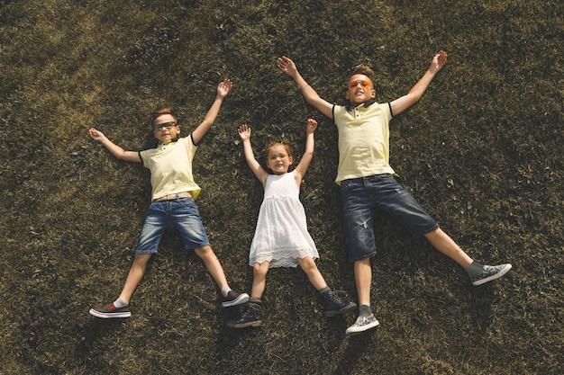 Deux frères et une sœur sont allongés sur l'herbe, les bras et les jambes tendus.