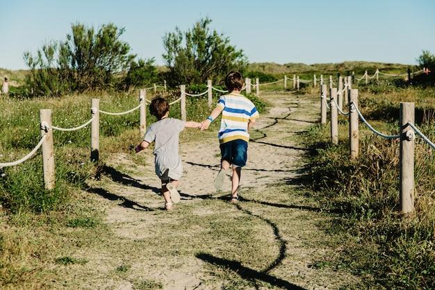 Deux frères et sœurs courent main dans la main dans un champ heureux et libre.