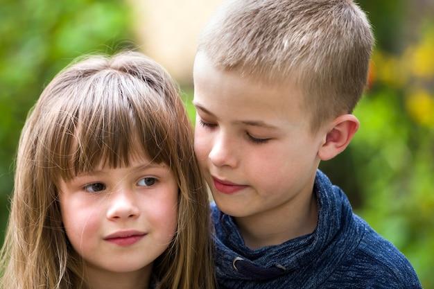 Deux frères et soeurs mignons enfants blonde, jeune garçon frère et soeur fille à l'extérieur sur le bokeh vert ensoleillé lumineux.