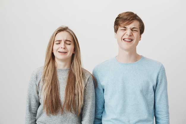 Deux frères et sœurs pleurnichards se plaignent. fille et mec grimaçant