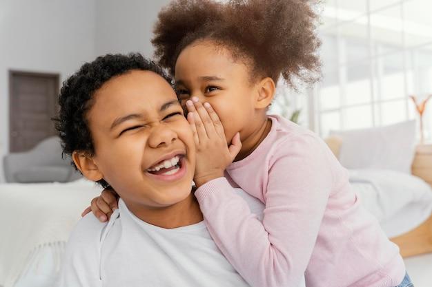 Deux frères et sœurs se racontant des secrets à la maison