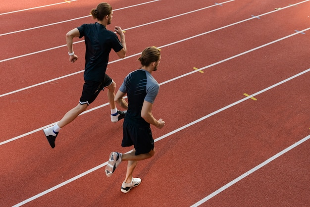 Deux frères sportifs jumeaux exécutant au stade à l'extérieur.