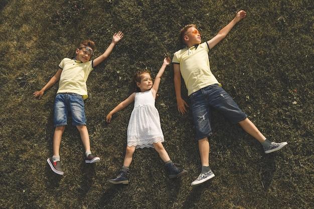 Deux frères en t-shirts jaunes et une sœur en robe blanche se trouvent sur l'herbe
