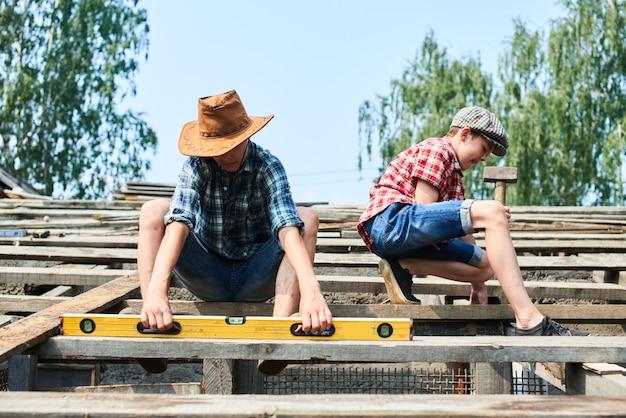 Deux frères en train de construire le toit d'une grange dans le village