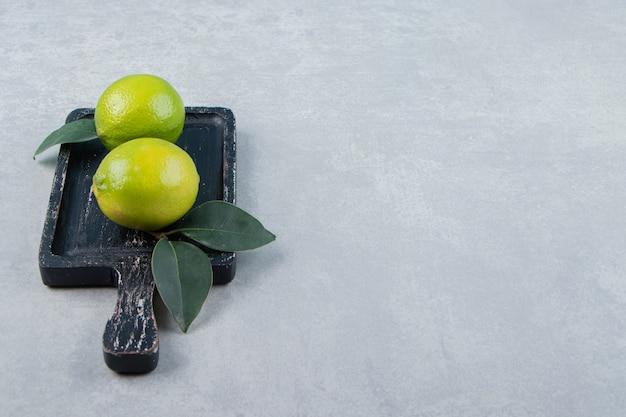 Deux fruits de citron vert avec des feuilles sur une planche à découper