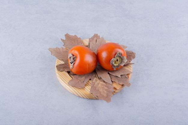Deux fruits de kaki frais et feuilles séchées sur plaque en bois.