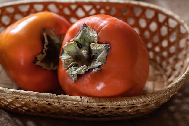 Deux fruits de kaki mûrs dans un panier en osier