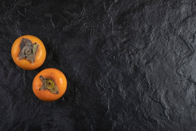 Deux fruits kakis mûrs placés sur une surface noire
