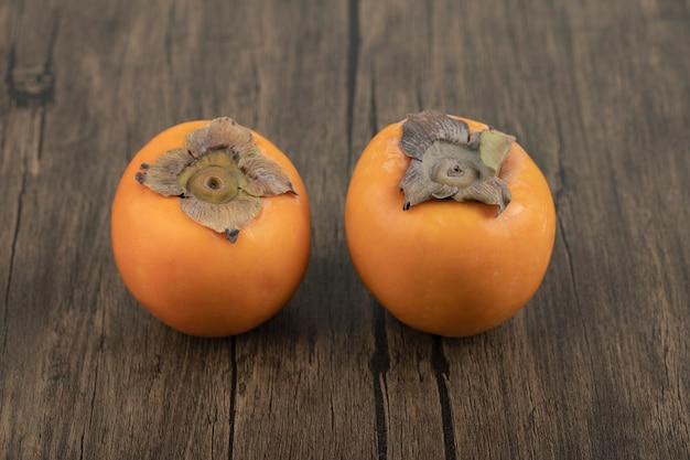 Deux fruits mûrs de kaki placés sur une surface en bois
