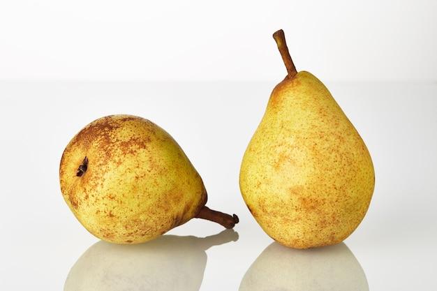 Deux fruits de poires jaune-vert juteux frais isolés sur fond blanc.