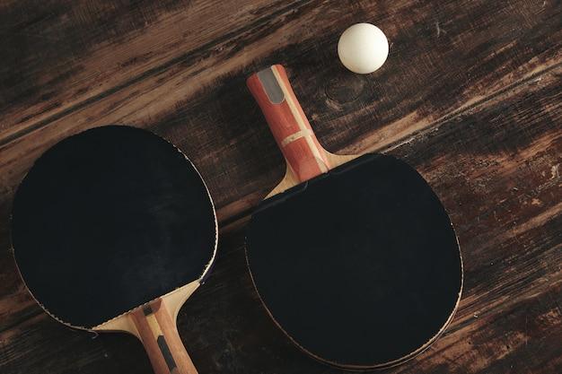 Deux fusées de ping-pong professionnelles allongées sur une table en bois vintage.