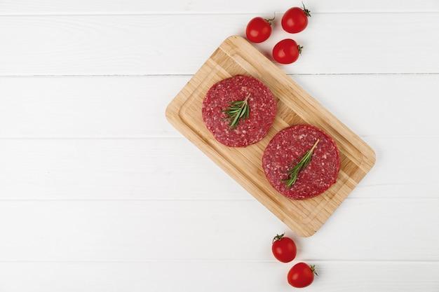 Deux galettes de bœuf cru sur planche de bois