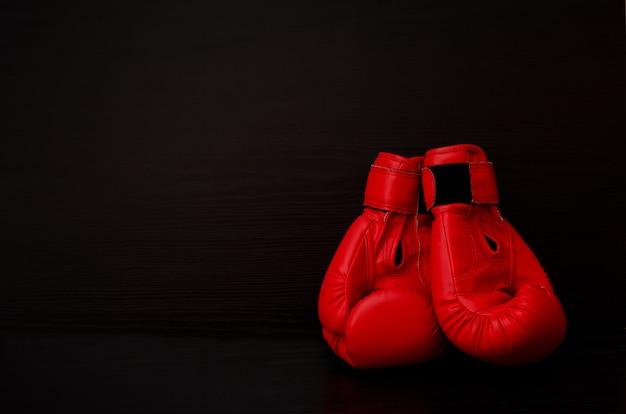 Deux gants de boxe rouges sur le côté du cadre sur fond noir, espace vide