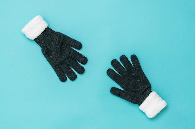 Deux gants pour femmes s'étirent l'un vers l'autre sur un fond bleu. le concept d'espoir et de rencontre. accessoires de mode pour femmes.