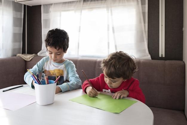 Deux garçon caucasien peint à l'intérieur d'une caravane lors d'un week-end