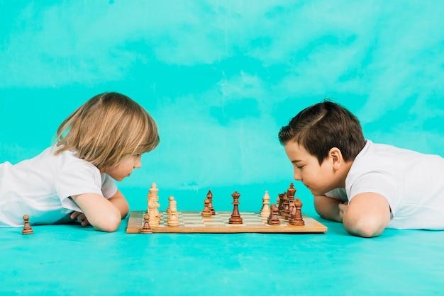 Deux garçon sérieux jouant aux échecs en studio, fond bleu