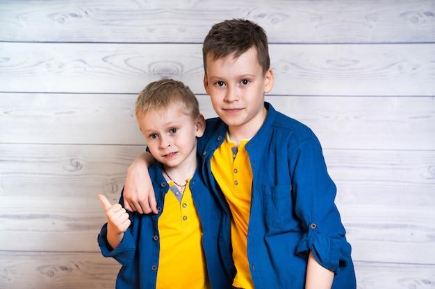 Deux garçons attrayants en chemises bleues et t-shirts jaunes posant ensemble. portrait de deux frères s'embrassant et regardant