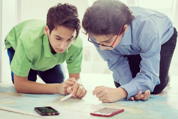 Deux garçons cherchant sur la carte du monde