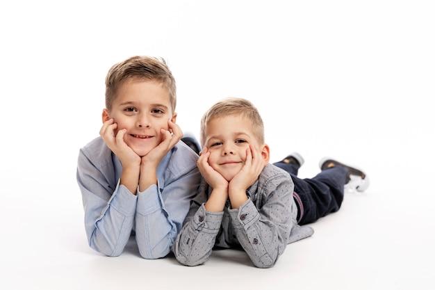 Deux garçons frères en chemises bleues gisent allongés, la tête dans les mains et souriant.