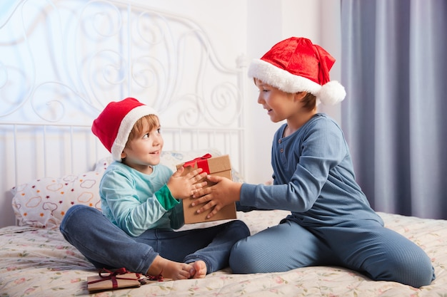 Deux garçons heureux avec boîte-cadeau de noël