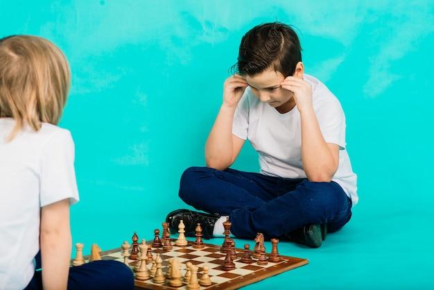 Deux garçons jouant aux échecs, fond de studio, sport