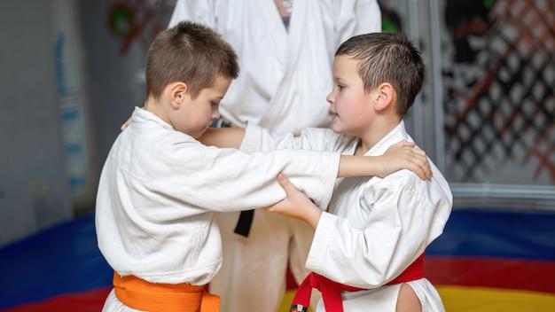 Deux garçons en kimono pratiquant les arts martiaux dans le ring d'une salle de sport