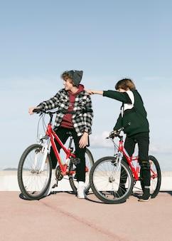 Deux garçons avec leurs vélos à l'extérieur