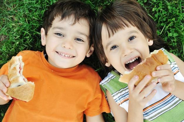Deux garçons mignons allongés sur le sol dans la nature et mangeant joyeusement des aliments sains