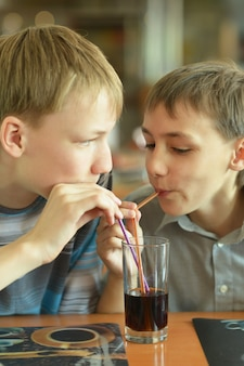 Deux garçons mignons buvant du coca au café