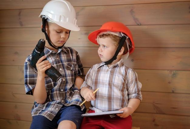 Deux garçons mignons dans des casques de construction discutent d'un plan pour les travaux à venir. les enfants jouent aux constructeurs. petit garçon avec un tournevis dans ses mains