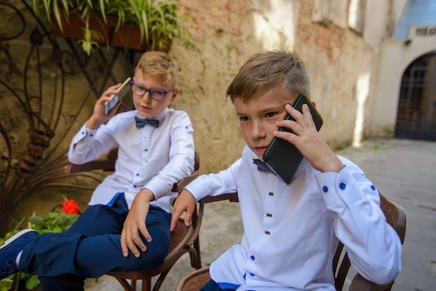 Deux garçons mignons parlent sur leur smartphone. les garçons imitent les parents des hommes d'affaires. les gars sont assis sur des chaises en bois dans la rue de la vieille ville.