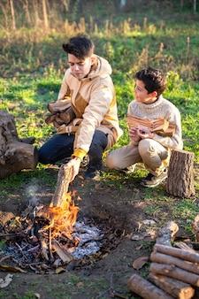 Deux garçons sur un pique-nique allumant un feu de camp avec des troncs, de l'herbe verte