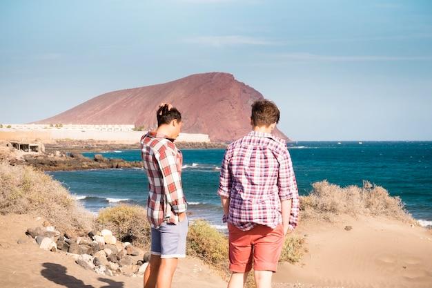 Deux garçons à la plage avec une voiture parlant ensemble et s'amusant face à la mer sans vagues - appréciant et concept de style de vie des voyageurs