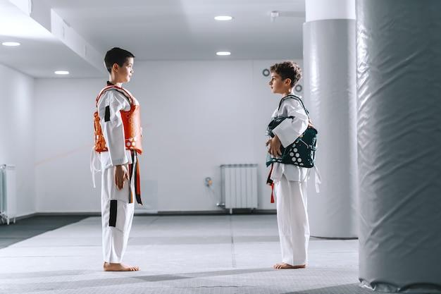 Deux garçons de race blanche dans des accessoires tekwondo debout et se regardant tout en se préparant au combat.