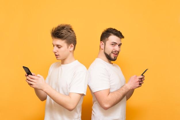 Deux garçons se tiennent dos à dos sur le jaune, tiennent les smartphones dans leurs mains, l'un regarde l'écran